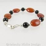 Red and black Agate bracelet on riser
