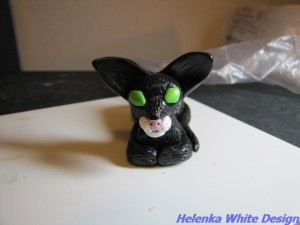 Black cat with folded paws - unbaked