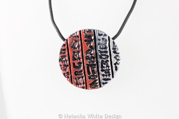 Round hieroglyph pendant in red and silver